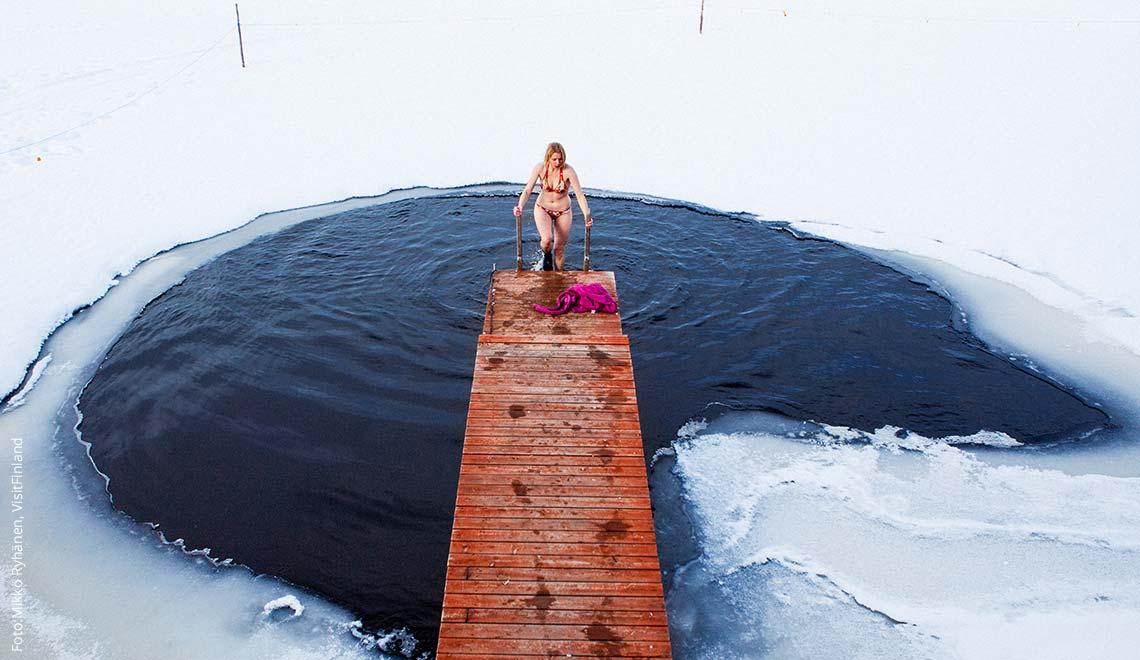 Frau im Bikini badet in Eiswasser